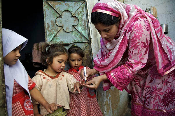 Pracownik medyczny znakuje palec dziewczynki, stojącej między swoimi dwiema siostrami, żeby zaznaczyć, że została zaszczepiona przeciwko polio, Karachi, Pakistan, luty 2011.
